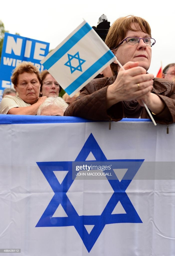 A participant holds an Israeli flag as she listens to speeches delivered during a rally against antiSemitism entitled 'Stand Up Jew Hatred Never...