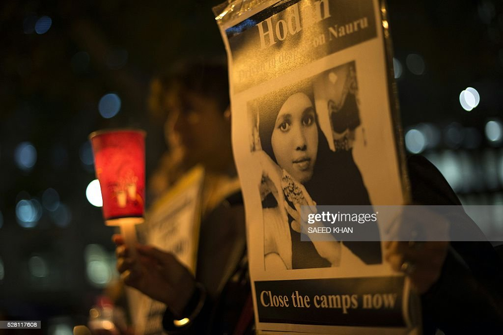 A participant holds portrait of a Somali refugee, who set herself on fire on the remote Pacific island of Nauru, during a candle light vigil in Sydney on May 4, 2016. More than 750 asylum-seekers held in a Papua New Guinea detention camp launched legal action on May 4, 2016 to be moved to Australia after a court in the Pacific nation found the centre unconstitutional. / AFP / SAEED