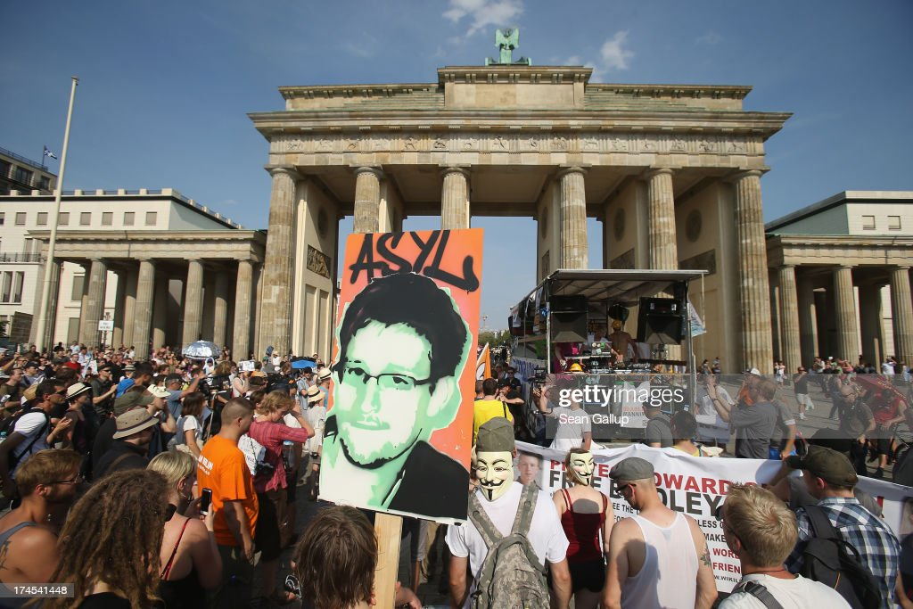 A participant holds up a picture of former NSA employee <a gi-track='captionPersonalityLinkClicked' href=/galleries/search?phrase=Edward+Snowden&family=editorial&specificpeople=10983676 ng-click='$event.stopPropagation()'>Edward Snowden</a> with the word 'asylum' written above it at a protest gathering in front of the Brandenburg Gate against the electonic surveillance tactics of the NSA on July 27, 2013 in Berlin, Germany. The NSA scandal has been especially contentious in Germany after media reports claimed the NSA had conducted wide scale gathering of electonic data, including e-mails, of German citizens. Activists are demonstrating against the NSA in cities across Germany today.