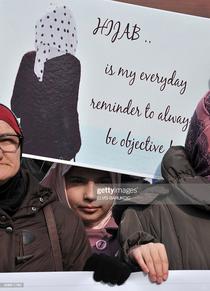 A participant holds up a placard as hundreds of Muslim women wearing the traditional Muslim headscarf also known as hijab protest in Sarajevo's historical center, on February 7, 2016. The protest walk was organized after a decision was made by Bosnia and Herzegovina's High Judicial Committee, that religious manifestations should neither be shown nor displayed, by judges, prosecutors or other personal of the judiciary institutions in the country. / AFP / ELVIS BARUKCIC