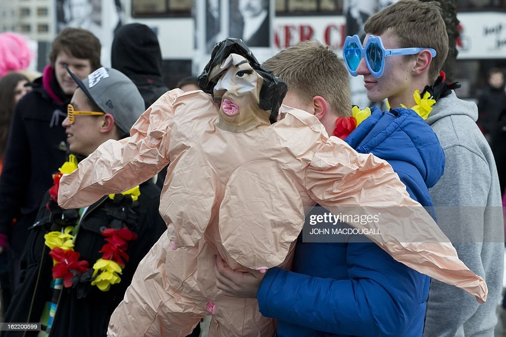 A participant in a flashmob blows up an inflatable sex doll as flashmobbers get ready to dance the Harlem Shake in front of the Berlin cathedral February 20, 2013. The flashmob was called in an effort to gather as many people as possible and perform the Harlem Shake in sub-zero temperatures. AFP PHOTO / JOHN MACDOUGALL