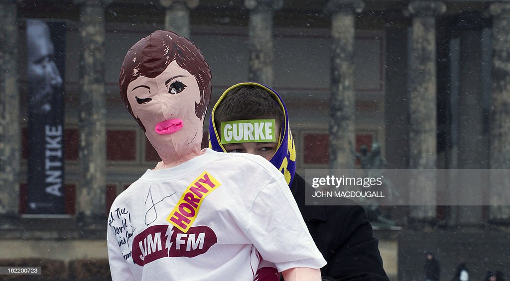 A participant in a flashmob blows up an inflatable sex doll as flashmobbers get ready to dance the Harlem Shake in front of the Berlin cathedral February 20, 2013. The flashmob was called in an effort to gather as many people as possible and perform the Harlem Shake in sub-zero temperatures.