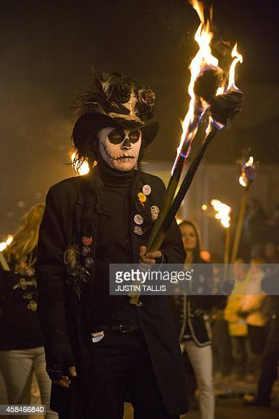 A participant in costume holds aloft a torch as bonfire societies parade through the streets of Lewes in Sussex on November 5 during the traditional...