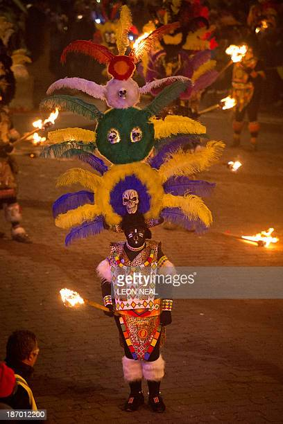 A participant in costume holds aloft torches during the Bonfire Night celebrations on November 5 2013 in Lewes Sussex in EnglandBonfire Night is...