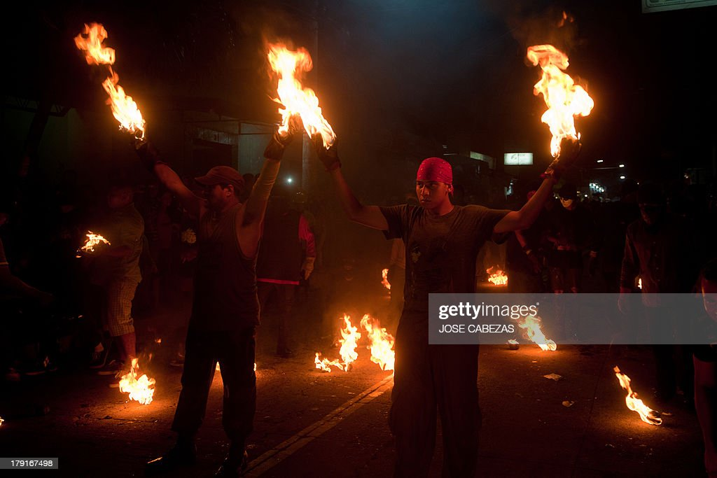 A participant in 'La Recuerda' (The Remembrance) festival raise fireballs in the main street of Nejapa, some 20 km north of San Salvador, on August 31, 2013. The Recuerda tradition, celebrated in honour of Saint Jeronimo, dates from 1922 and recalls the 1658's eruption of the San Salvador volcano that destroyed Nejapa. AFP PHOTO/ Jose CABEZAS