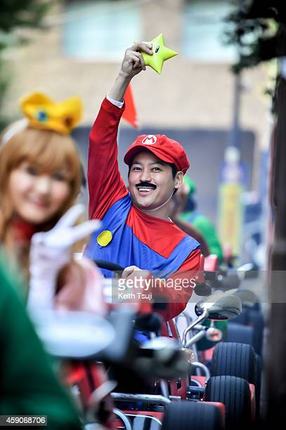 Participant in Mario costume gets ready for the Real Mario Kart event in Tokyo on November 16 2014 in Tokyo Japan The organizer calls for...