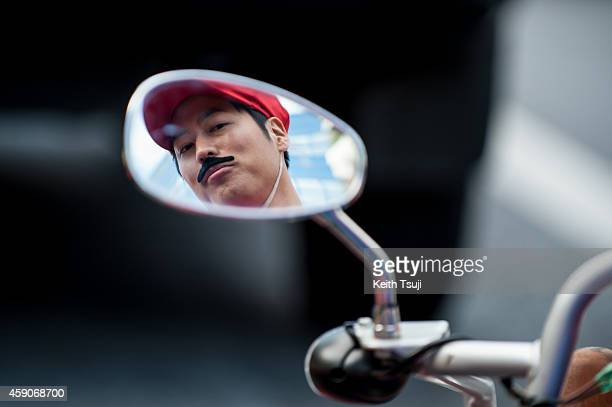 Participant in Mario costume looks in a mirror at the Real Mario Kart event in Tokyo on November 16 2014 in Tokyo Japan The organizer calls for...