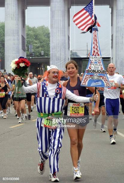 A participant in the Berlin Marathon dressed as the French cartoon figure Obelix holds a model of the Eiffel Tower with a US flag as he passes the...