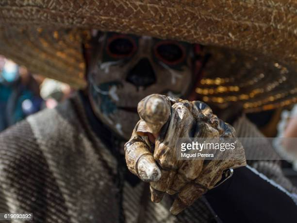 A participant in the parade during the Day of the Dead Celebrations in Mexico City feature a deadly skull while pointing at the crowd