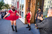 Participant in the Red Dress Bar crawl an AIDS fundraiser poses for photographs by a local shopkeeper on Castro Street Following the Orlando shooting...