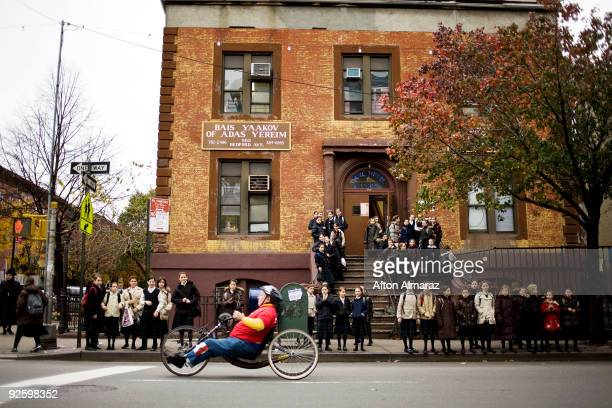 A participant in the wheelchair division of the 40th ING New York City Marathon passes by a group of Hasidic Jewish girls in the Williamsburg section...