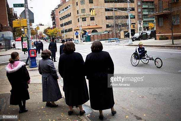 A participant in the wheelchair division of the 40th ING New York City Marathon passes by a group of Hasidic Jewish woman and men in the Williamsburg...