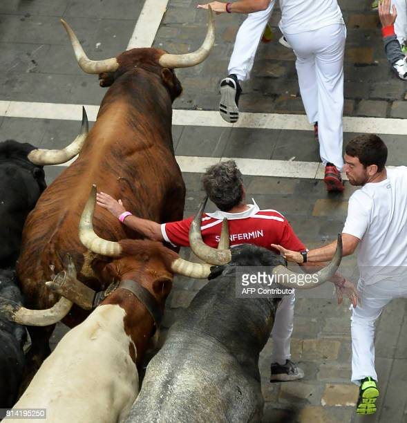 A participant is hit by a bull as others run ahead of Miura's fighting bulls during the eighth and last bull run of the San Fermin festival in...