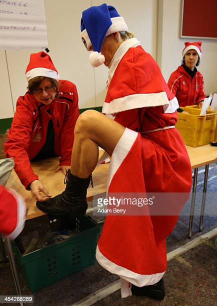 A participant is shown how to wear her shoe chip to register her performance in 5th annual Michendorf Santa Run on December 8 2013 in Michendorf...
