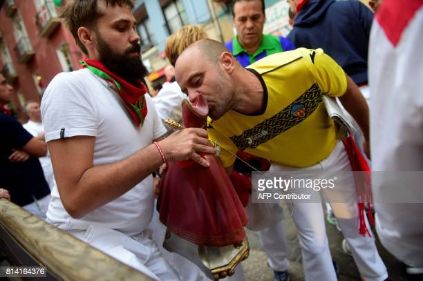 A participant kisses the figure of San Fermin as he waits with others for the Miura's fighting bulls before the eighth and last bull run of the San...