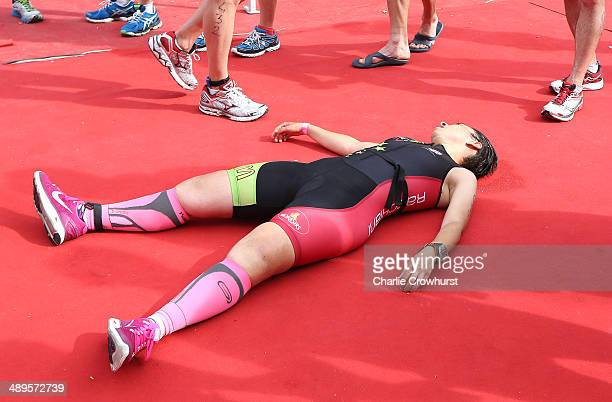 A participant lays on the floor at the finish line exhausted after completing the race during the Challenge Triathlon Rimini on May 11 2014 in Rimini...