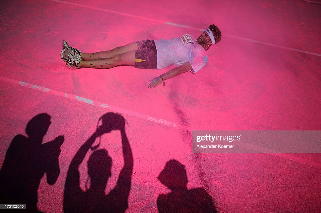 A participant lies in the pink powder as he passes through the pink colour zone during the Color Run at the Hanover Fairgrounds on July 7, 2013 in Hanover, Germany. The Color Run is a 5km run during which participants, who dress in white, have a different colored cornflour based powder thrown at them for every kilometer that they run. This was the second Color Run to be held in Germany, attacting 5000 runners.
