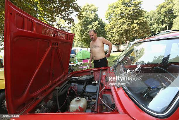 A participant looks at the engine of his Lada 1200 automobile at a Trabant enthusiasts' weekend on August 8 2015 near Nossen Germany The Trabant also...