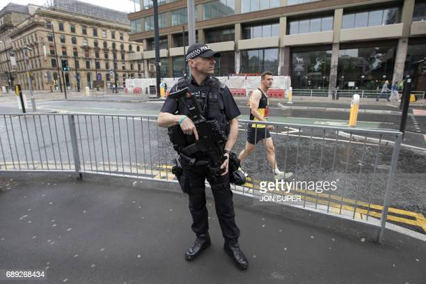 A participant makes his way past an armed police officer on his way to the start of the Great Manchester Run in Manchester on May 28 2017 Britain...