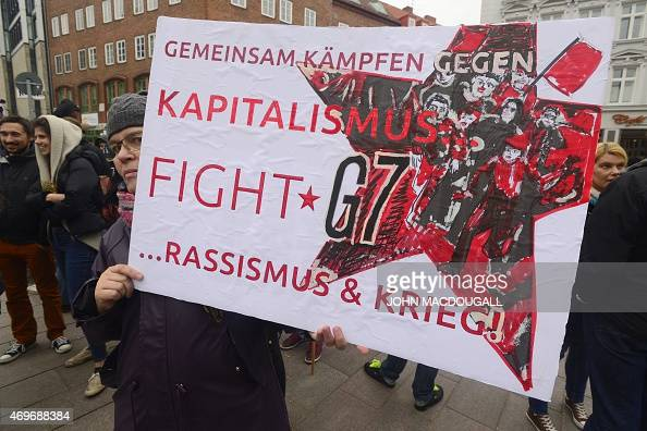 Participant of a demonstration against G7 foreign ministers meeting holds a banner that calls for a fight against capitalism racism and war in...