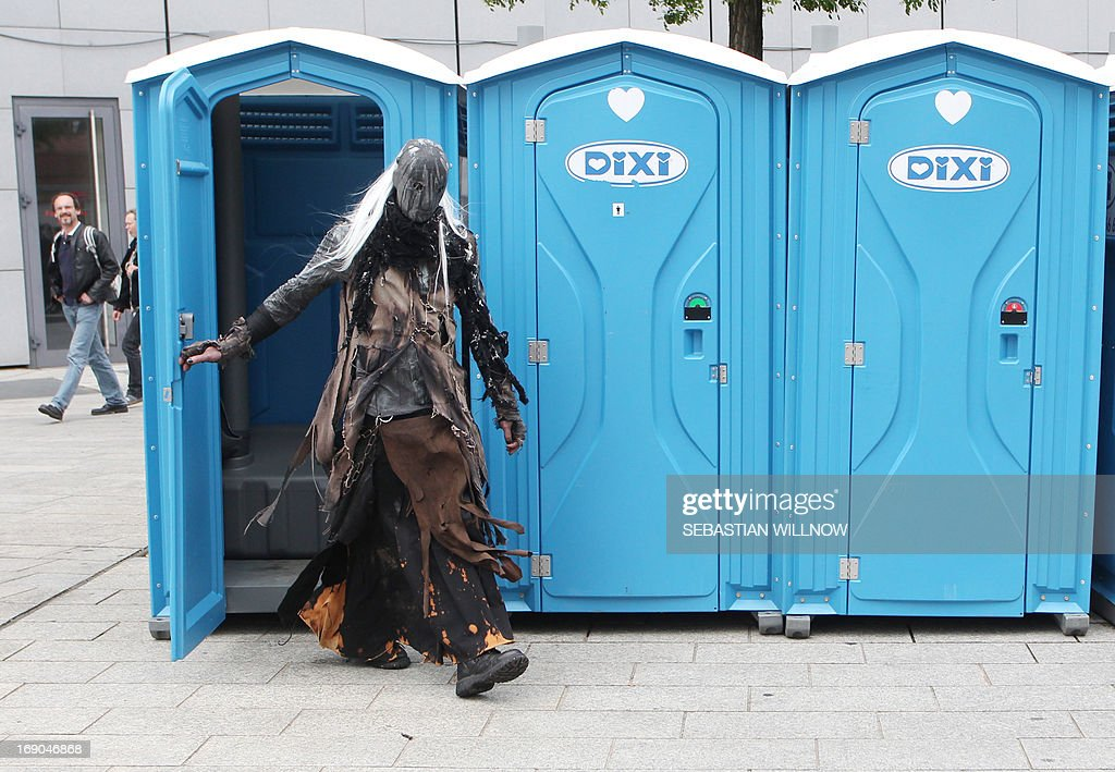 A participant of a Wave-Gothic meeting leaves a port-a-potty on May 19, 2013 in Leipzig, eastern Germany. Organisers expect some 20,000 visitors from all over the world for the 'dark' music and arts festival running until May 20, 2013. AFP PHOTO / SEBASTIAN WILLNOW GERMANY OUT
