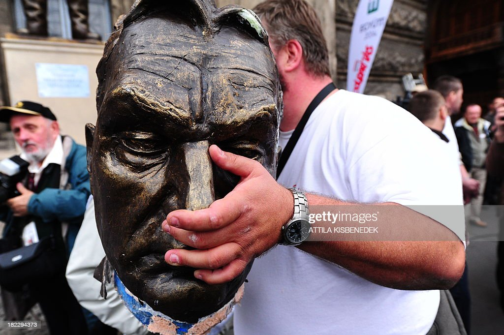 A participant of Hungarian 'Szolidaritas' Movement demonstration holds the head of the broken plastic statue of Hungarian Prime Minister Viktor Orban, representing the former Soviet communist dictator Stalin, in Budapest on September 29, 2013 during their anti-government demonstration to protest against the financial and economic policy of the Orban's government.