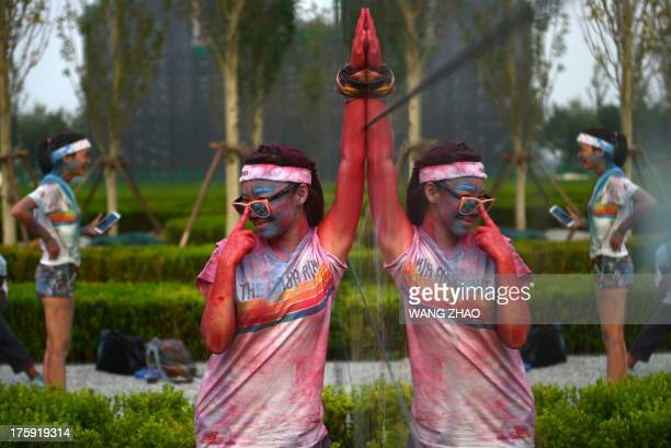 A participant of The Color Run Beijing is reflected in a mirror as she poses for a photograph after the event in Beijing on August 10 2013 Several...