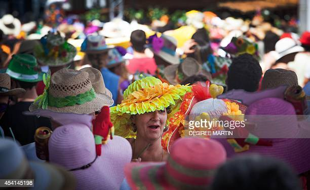 A participant of the Fair of the Pamela wearing a fancy hat reacts in a street of Tejina on the Spanish Canary island of Tenerife on August 25 2014...