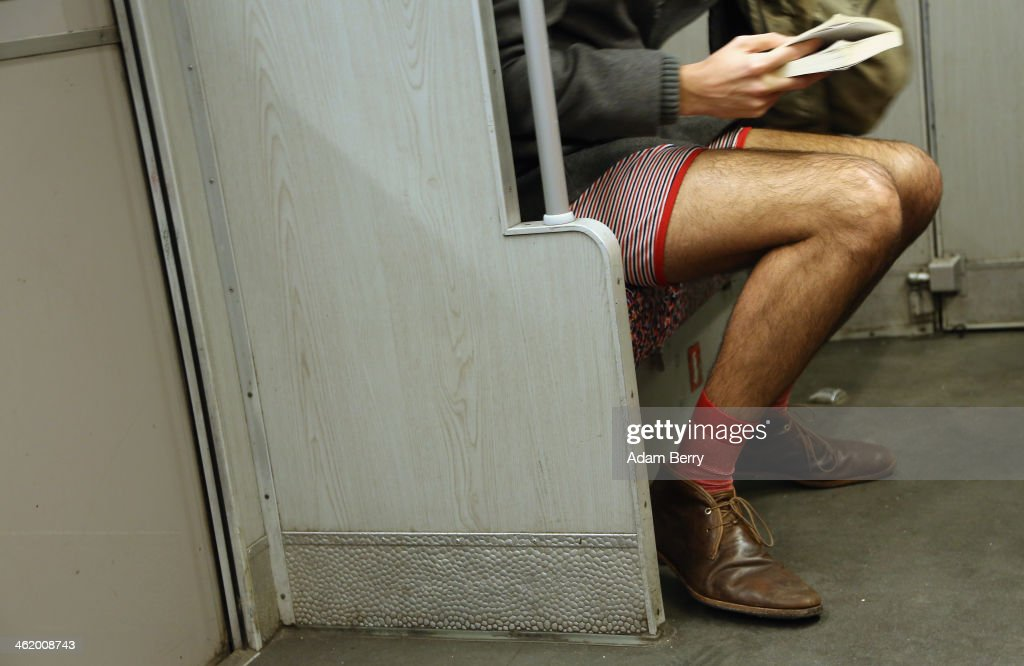 A participant of the No Pants Subway Ride reads a book while riding a train on January 12 2014 in Berlin Germany The annual event in which...