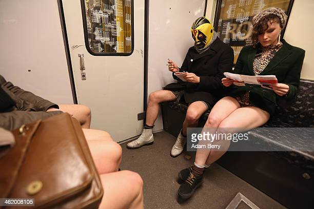 A participant of the No Pants Subway Ride wearing a luchador or Mexican wrestler mask sits next to another looking at a subway map as they ride a...