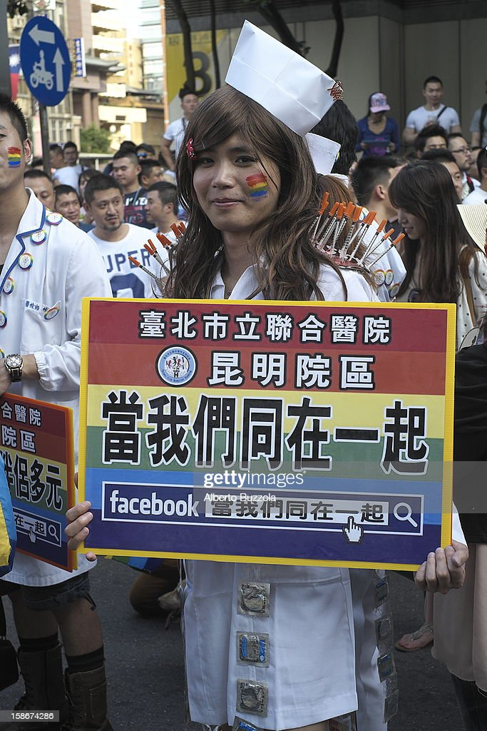"""A participant of the Taipei Gay and Lesbian Pride Parade holding a placard in Chinese that says : """"we of the homosexual community are all together""""."""