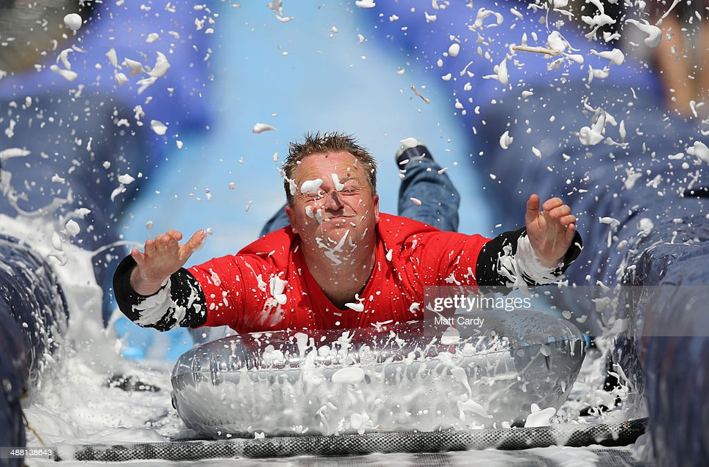 A participant on a lilo slides down a giant water slide that has been installed down Park Street on May 4, 2014 in Bristol, England. The 90m (295ft) slide was made from plastic sheets, hay bales, water and washing-up liquid and was the brainchild of artist Luke Jerram. The three hundred ticket holders who were picked from nearly 100,000 applicants took turns to hurtle down the slide watched by hundreds of spectators lining the street that was closed to traffic.