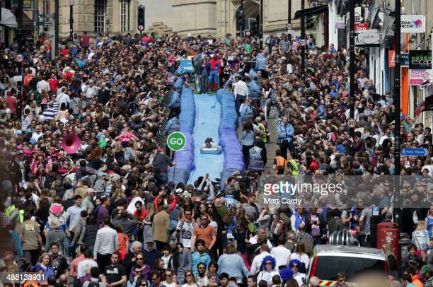 A participant on a lilo slides down a giant water slide that has been installed down Park Street on May 4 2014 in Bristol England The 90m slide was...