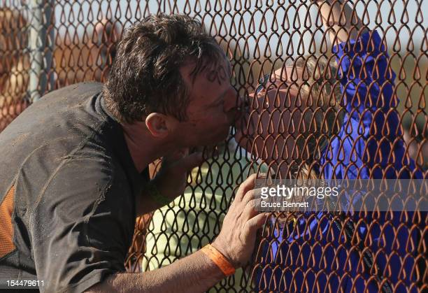 A participant pauses for a kiss during the Tough Mudder event at Raceway Park on October 20 2012 in Englishtown New Jersey