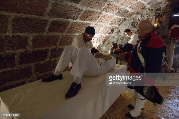 A participant playing the role of a injured Spanish soldier is attended during a historical reenactment of a battle between Spanish and British...