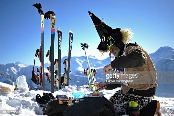 A participant prepares a cheese raclette during the 30th edition of the Belalp Witches Ski Race on January 14 2012 in Belalp Switzerland The race is...