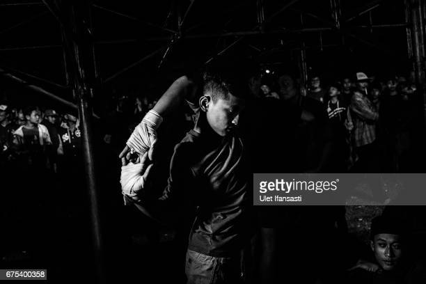 A participant prepares himself before his fight during Pencak Dor competition at the yard of Lirboyo islamic boarding school on April 29 2017 in...