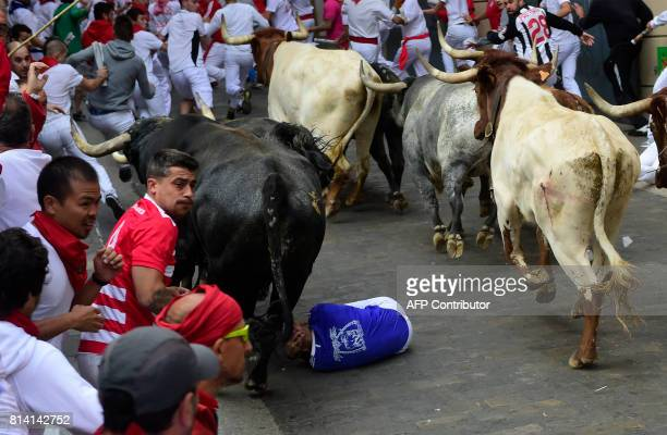 A participant protect his head after falling as other run ahead of Miura's fighting bulls during the eighth and last bull run of the San Fermin...