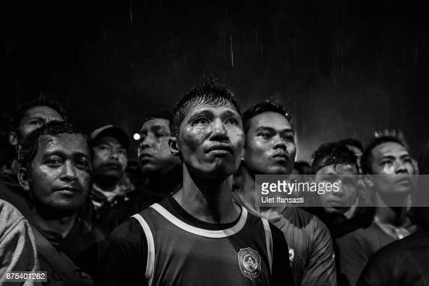 A participant reacts as he watches his friend during Pencak Dor competition at the yard of Lirboyo islamic boarding school on April 29 2017 in Kediri...
