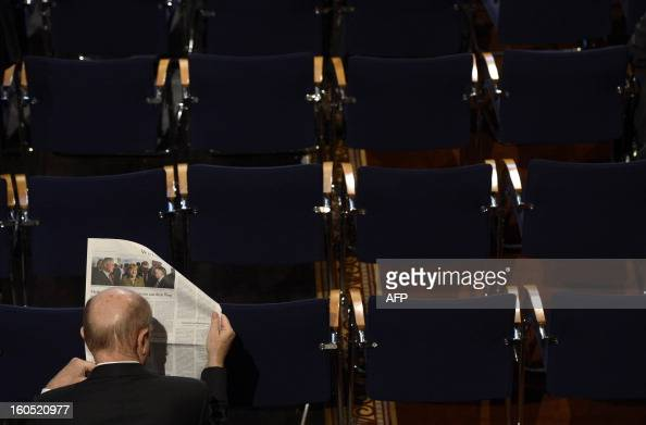 A participant reads a newspaper ahead the start of the second day of the 49th Munich Security Conference on February 2 2013 in Munich southern...