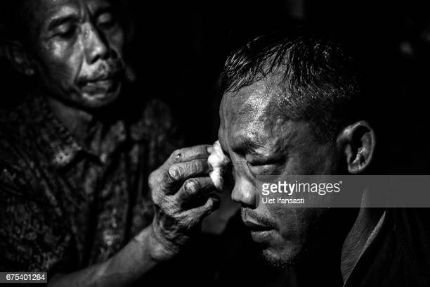 A participant receives treatment after his fight during Pencak Dor competition at the yard of Lirboyo islamic boarding school on April 29 2017 in...