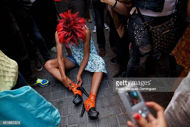 A participant removes his highheel shoes as he finished competing on the annual highheel race during Madrid Gay Pride celebrations in a street of...