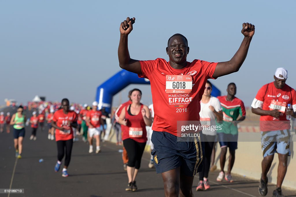 A participant runs in Dakar on February 14, 2016 during the first ever Dakar International Marathon long 42,195km. The competition organised by the BTP Eiffage society started on February 13 in front of International Conference Center Abou Diouf (Cicad) on the outskirts of Dakar with different runs of 10 km and will end the day after, February 14, with a marathon. The BTP Eiffage society hosted the event to celebrates its 90 years of presence in Senegal. / AFP / SEYLLOU