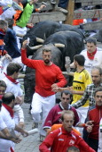 A participant runs in front of Jandilla's bulls as he takes a 'selfie' during the fifth bullrun of the San Fermin Festival in Pamplona northern Spain...