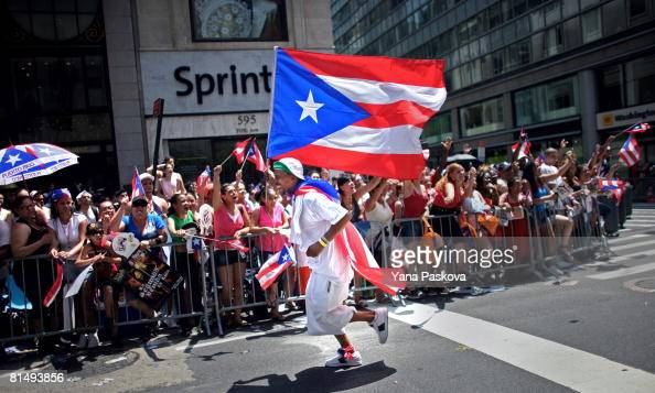 A participant runs in front of the crowd with the Puerto Rican flag in the annual Puerto Rico Day Parade June 8 2008 in New York City The parade...