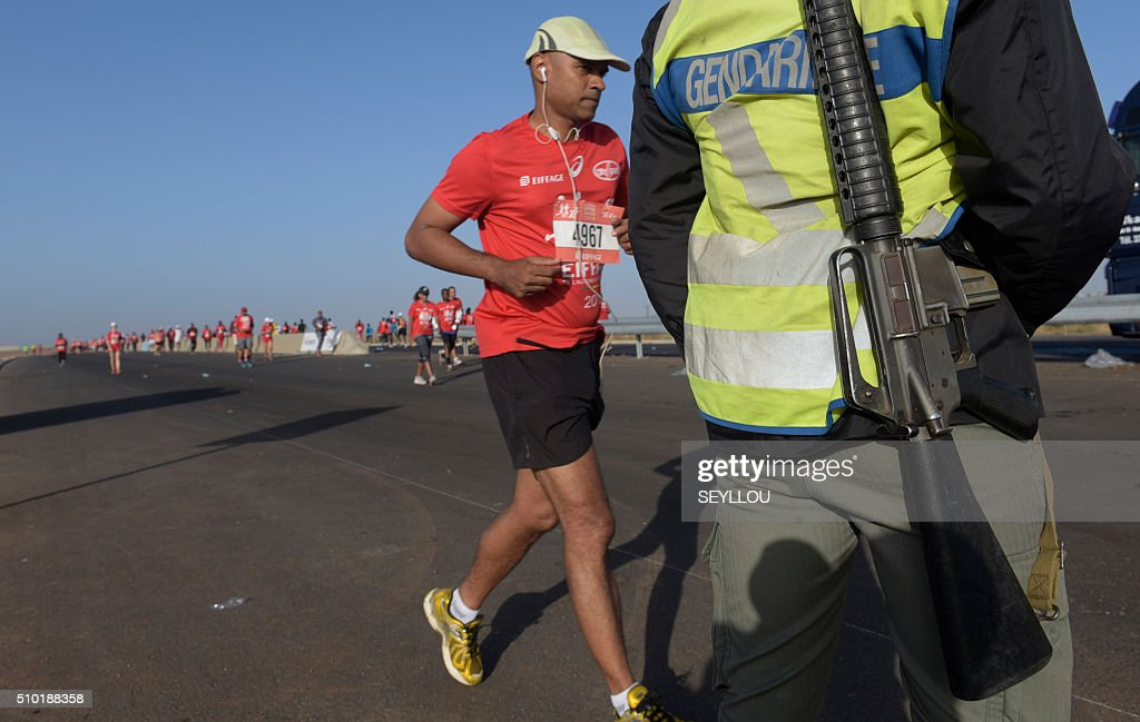 A participant runs next to a gendarme in Dakar on February 14, 2016 during the first ever Dakar International Marathon long 42,195km in 2h 16mm 37s according to official results. The competition organised by the BTP Eiffage society started on February 13 in front of International Conference Center Abou Diouf (Cicad) on the outskirts of Dakar with different runs of 10 km and will end the day after, February 14, with a marathon. The BTP Eiffage society hosted the event to celebrates its 90 years of presence in Senegal. / AFP / SEYLLOU