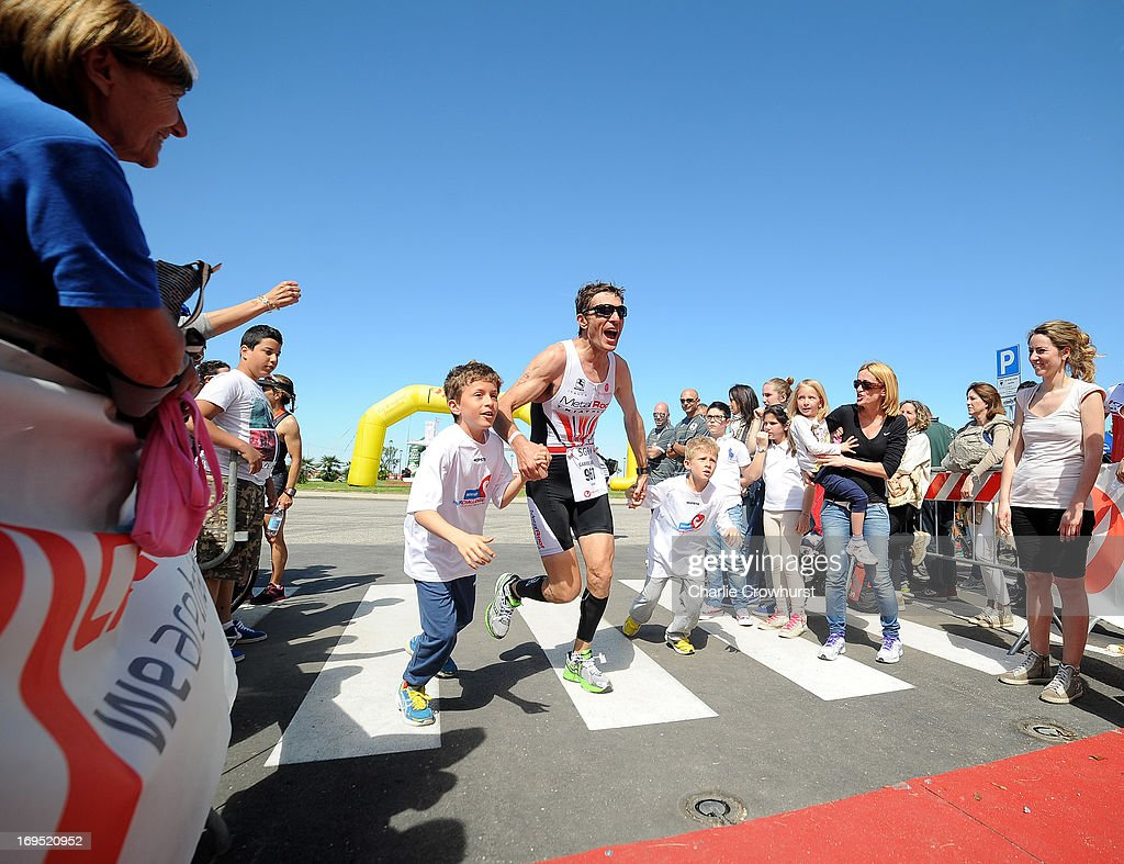 Participant runs the home straight with his children during the Challenge Family Triathlon Rimini on May 26, 2013 in Rimini, Italy.