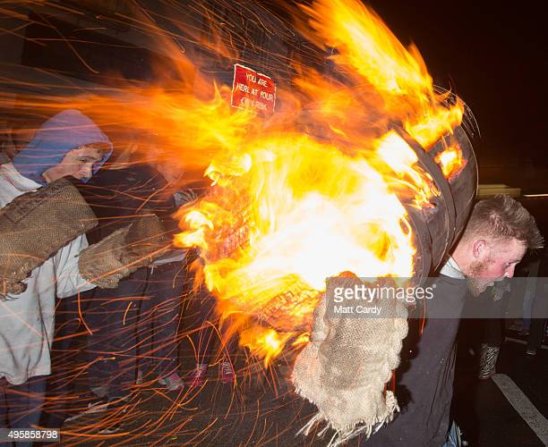 A participant runs with a burning barrel soaked in tar at the annual Ottery St Mary tar barrel festival on November 5 2015 in Ottery St Mary England...