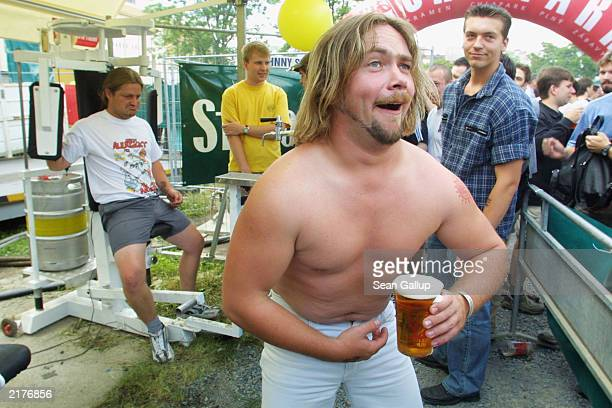 A participant shows off his beer muscles after lifting a full keg of beer on a weight machine during a street party at the Staropramen brewery June...