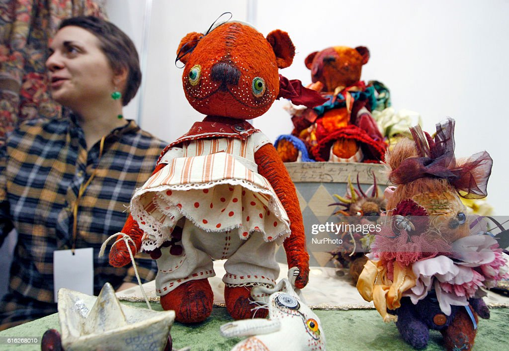 """A participant sits next the dolls,during International exhibition of dolls and Teddy called """"Fashionable Doll"""" in Kiev,Ukraine,21 October,2016. The event gathered together masters and artists from Ukraine and EU countries,which presented more than two thousand author dolls made in the various techniques. The exhibition will run from 21 till 23 October."""